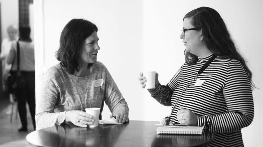 Kvinnor minglar med kaffemuggar i händerna.