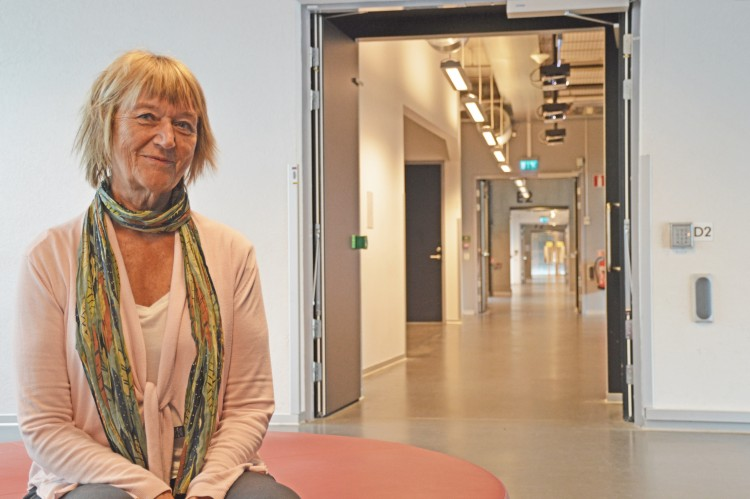 Ingegerd Tallberg Broman sitter på en röd sittpuff framför en korridor som fortsätter bortåt.