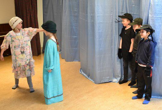 Barn utklädda spelar teater.