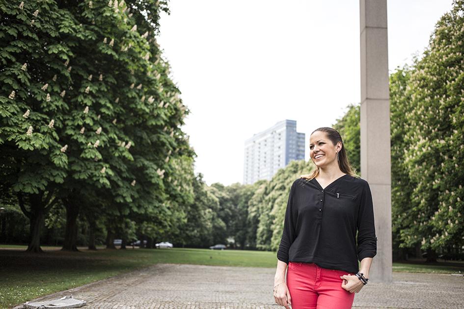 Kvinna står i park i Malmö där Kronprinsen syns bakom.