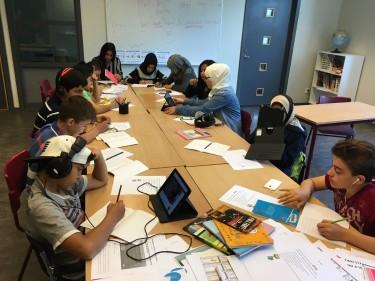Elever sitter runt bord och arbetar.