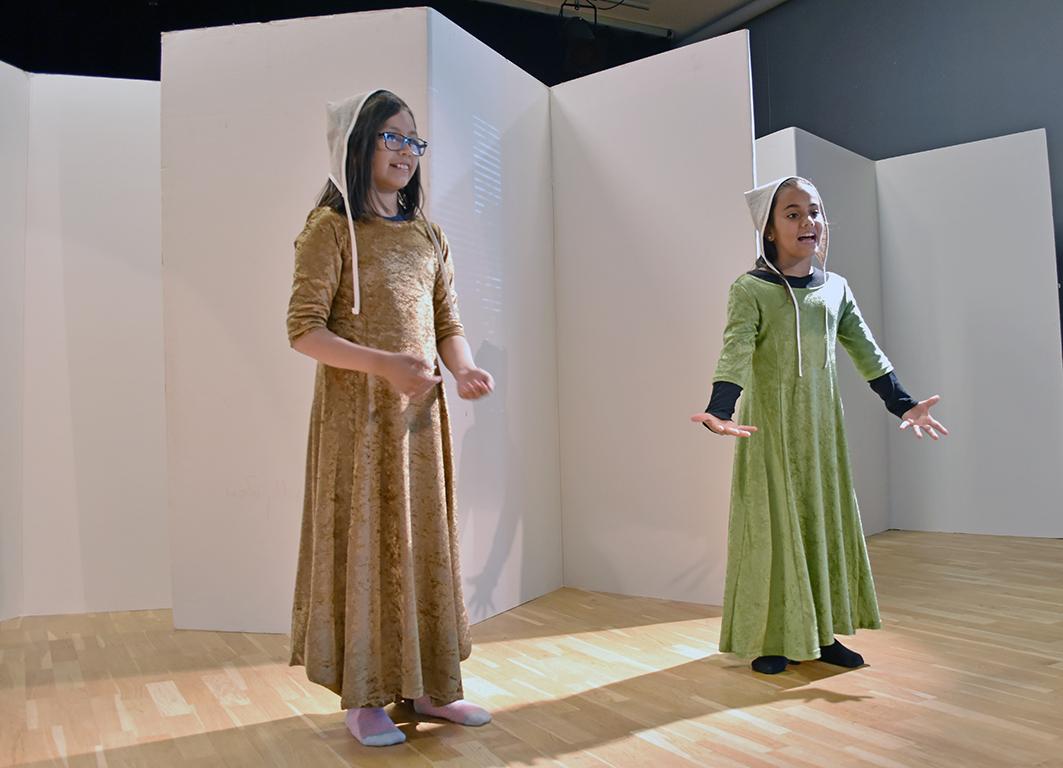 Två flickor i medeltida kläder står på scen och spelar teater.