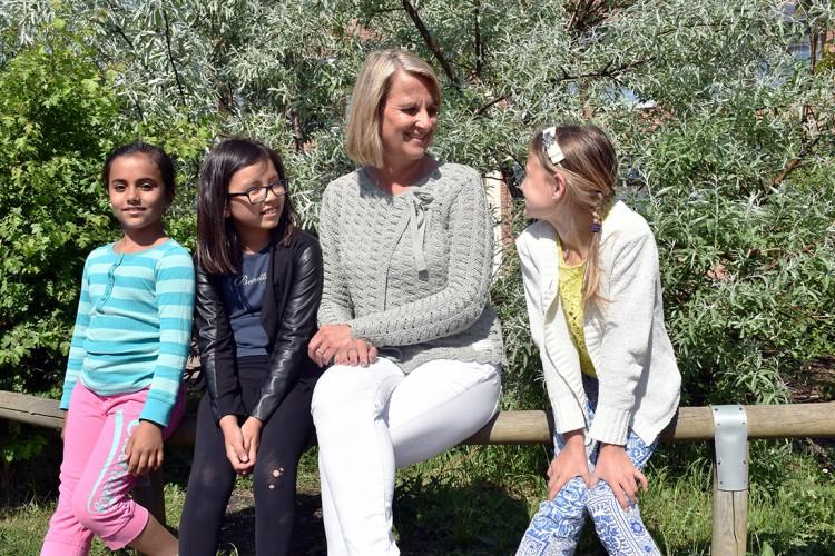 Pedagog och tre elver sitter på en bänk och tittar på varandra.