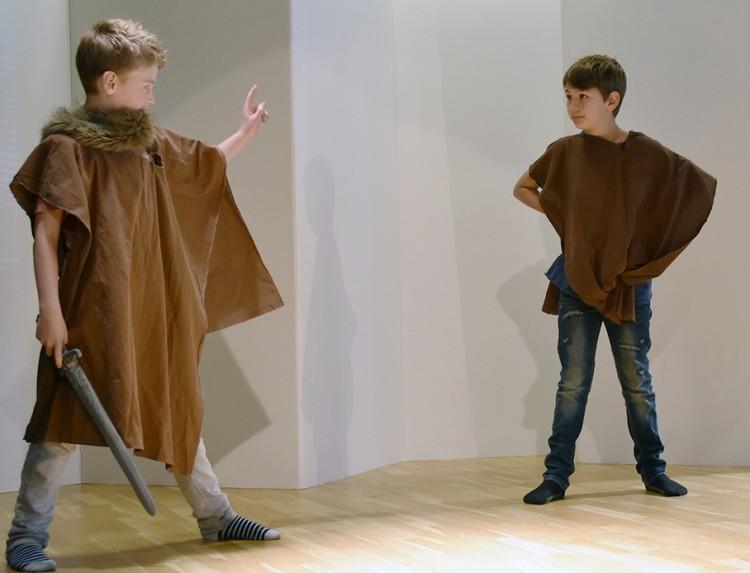 Två pojkar klädda i vikingakläder spelar teater.