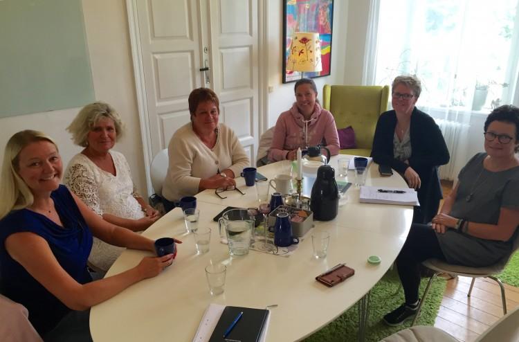 Sex kvinnor runt ett ovalt bord.