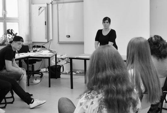 Kvinna framför elevgrupp i klassrum.