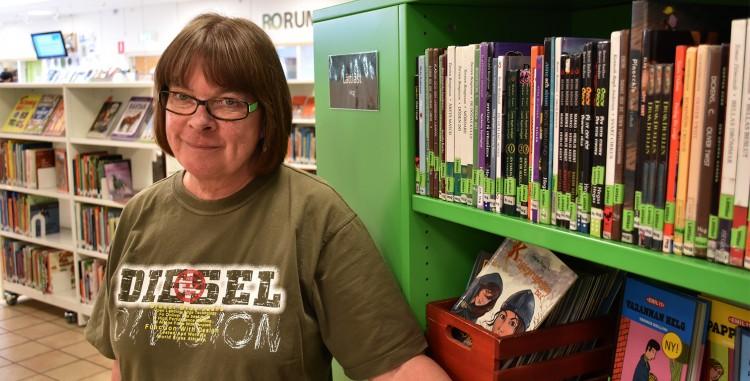 Ulla står framför bokhylla.