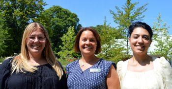 Tre kvinnor ler medan solen skiner.