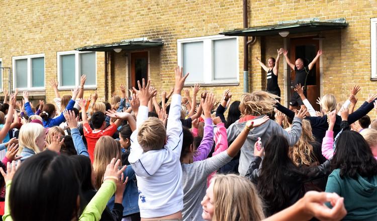 Elever på skolgård sträcker upp händerna och hoppar.