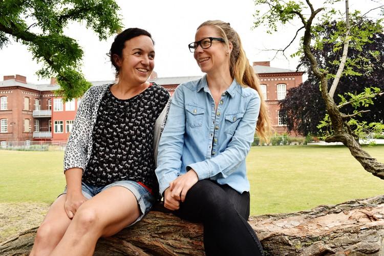 Två kvinnor sitter på en stock.