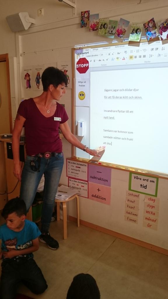 Pedagog visar på tavlan där begrepp projiceras.