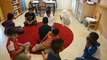 Elever sitter på golvet och samtalar.
