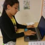 Elev skriver på uppfälld laptop.