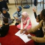 Elever sitter och golv och räcker upp händerna.