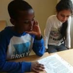 Elever sitter och läser vid bord.