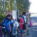 Elever står och väntar vid busshållplats.