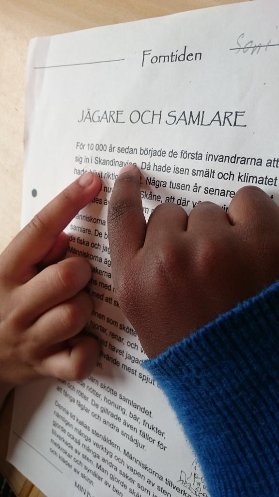 Barnhänder ligger på papper.