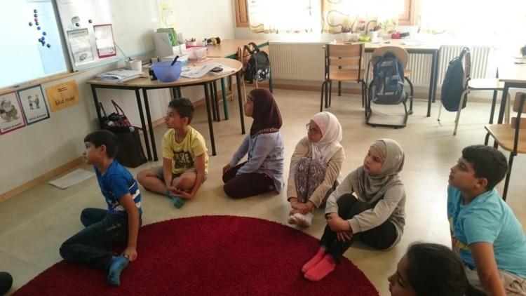 Elever sitter på golvet och tittar på tavlan.