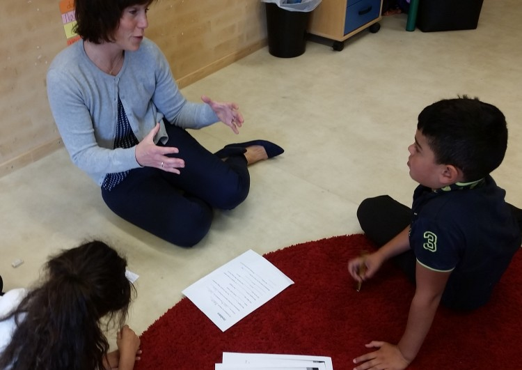 Pedagog sitter på golv tillsammans med elev och förklarar.