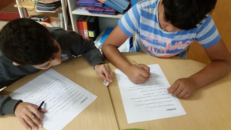 Elever sitter vid bord och jobbar.