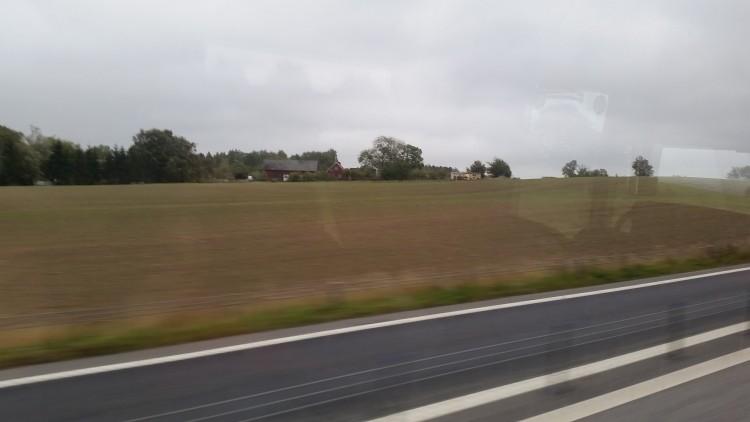 Vy över landskap från bussfönster.