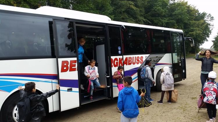 Barn hoppar ut ur buss.