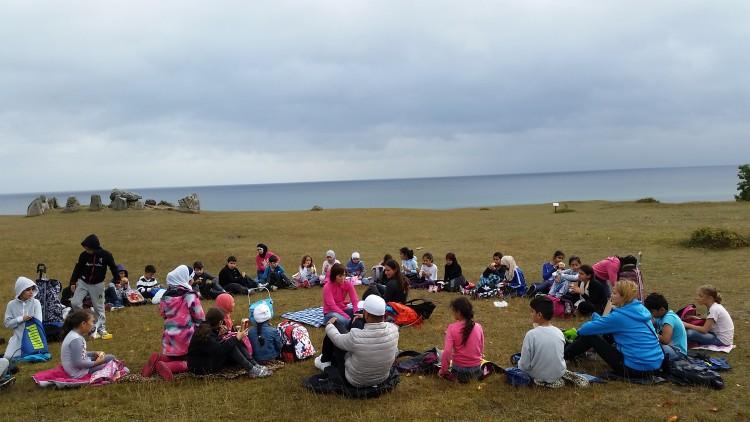 Klass och pedagoger sitter samlade vid havet.