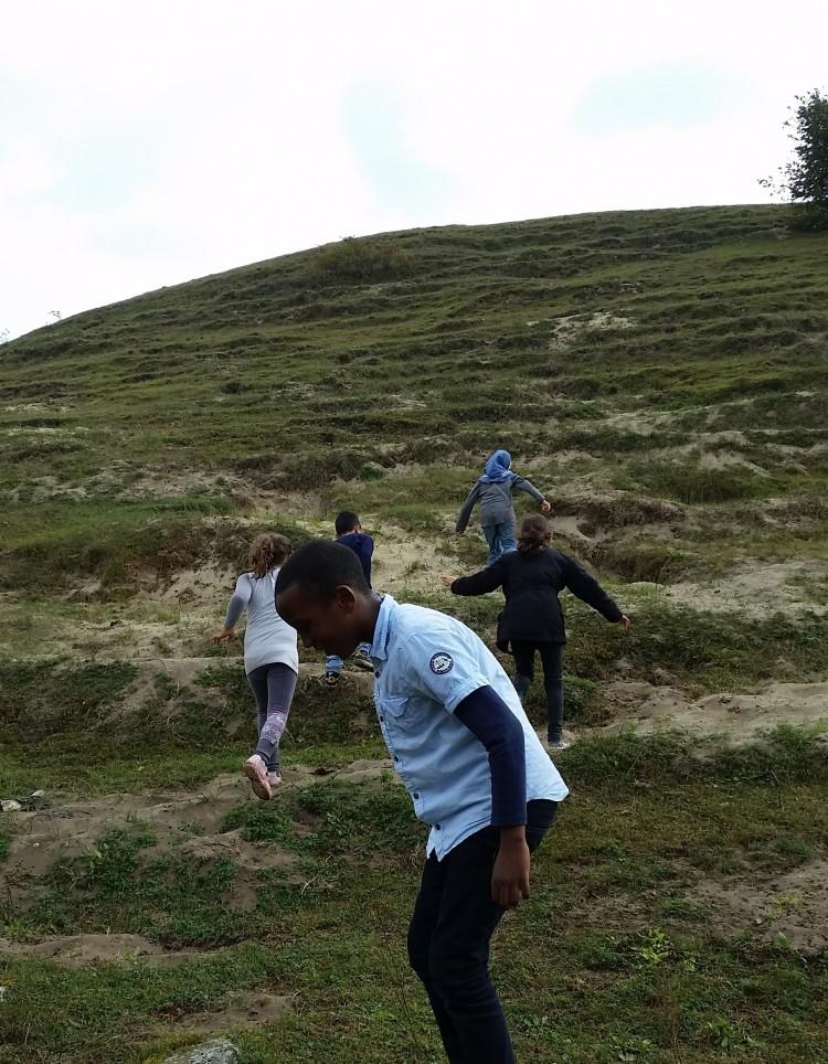 Barn springer upp för hög gräskulle.