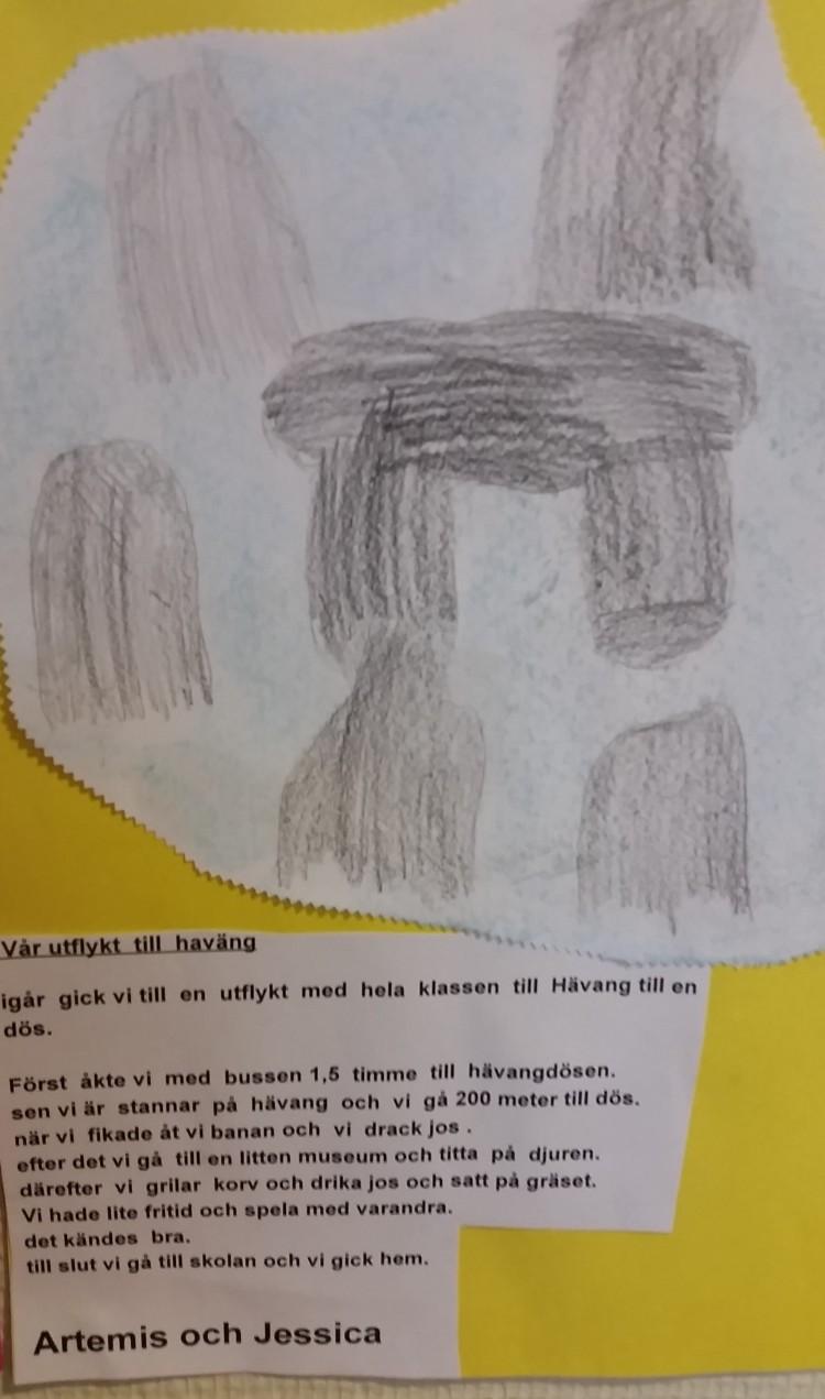 Lapp med återberättande text och teckning uppsatt på vägg.