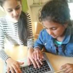 Två elever skriver på dator.