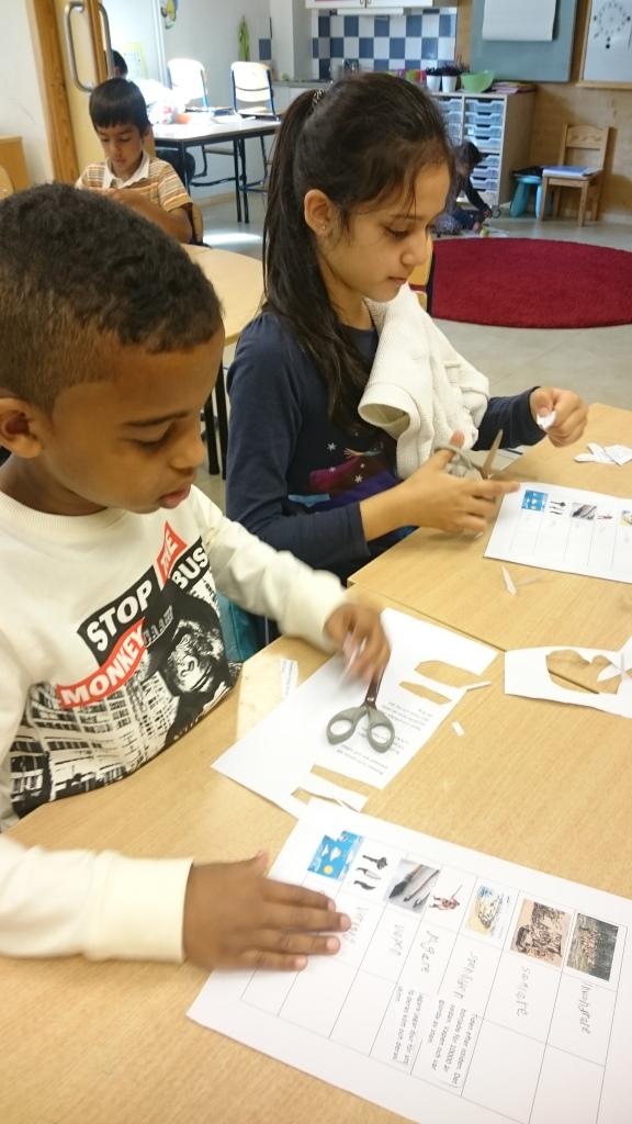 Två elever klipper och klistrar.