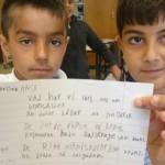 Två elever håller upp text de har skrivit.