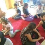 Barnen sitter på golvet.