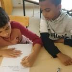 Två elever sitter och jobbar vid bord.