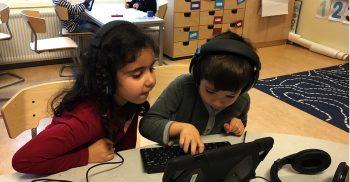 Två elever sitter vid bord och jobbar med ipad.