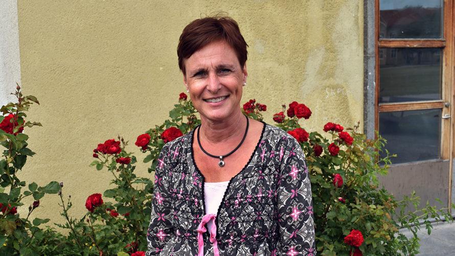 Kvinna står framför rosbuske.