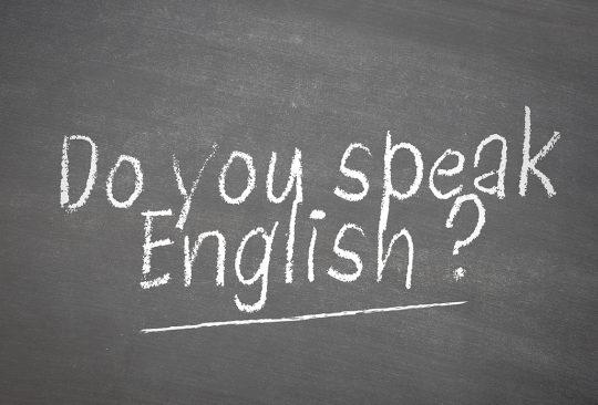 Svart tavla där det står skrivet Do you speak english?