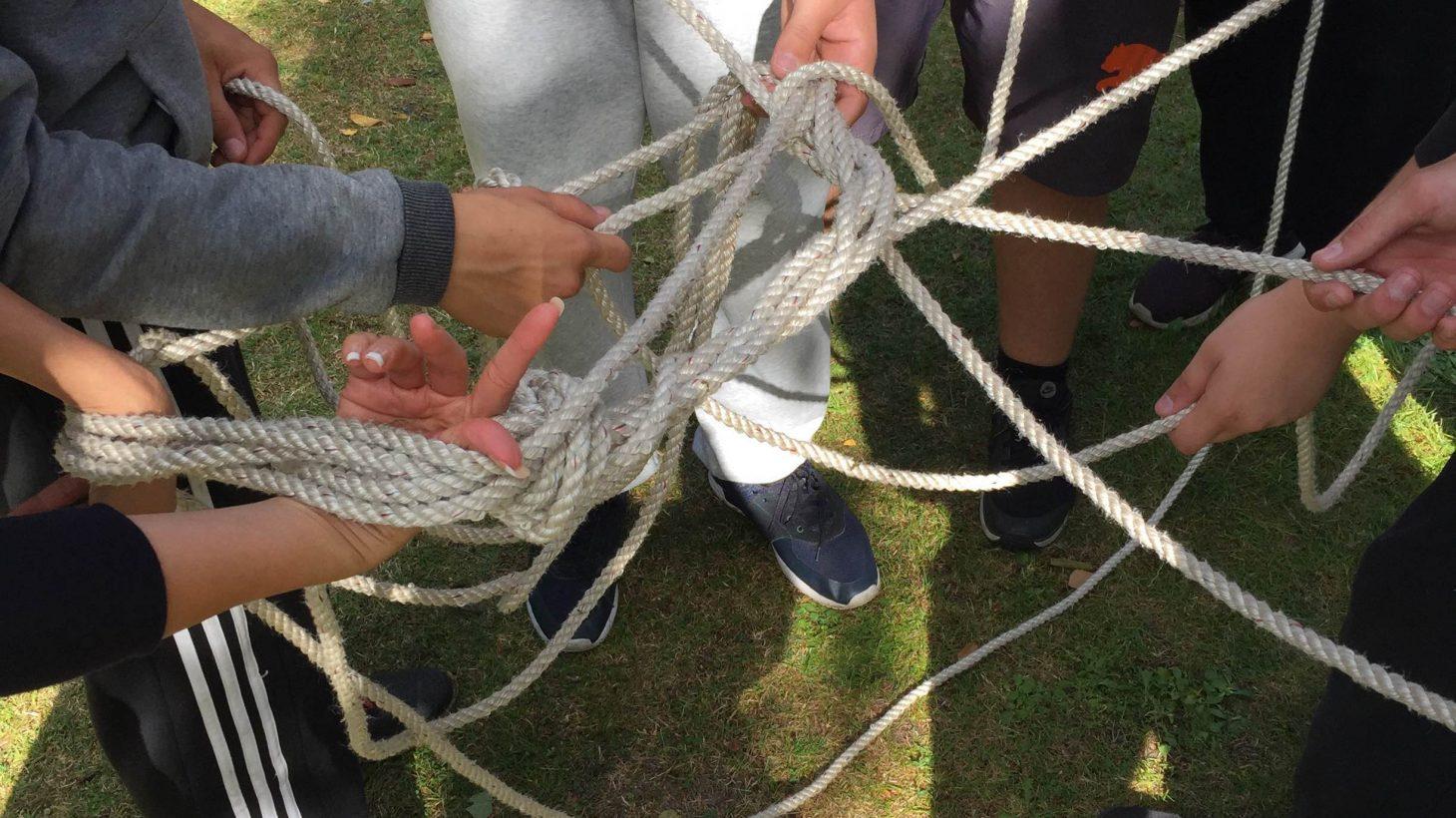 Händer håller ihop stor knut av rep.