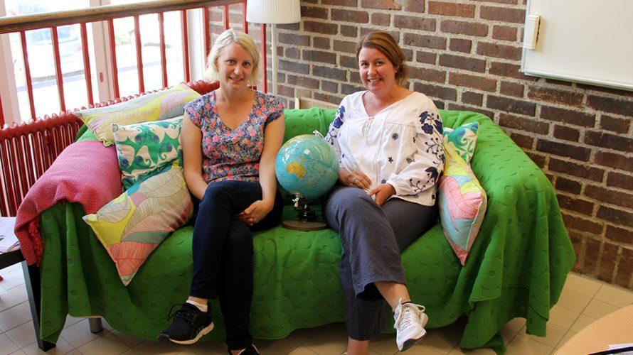Johanna och Kristina sitter i soffa med jordglob mellan sig.