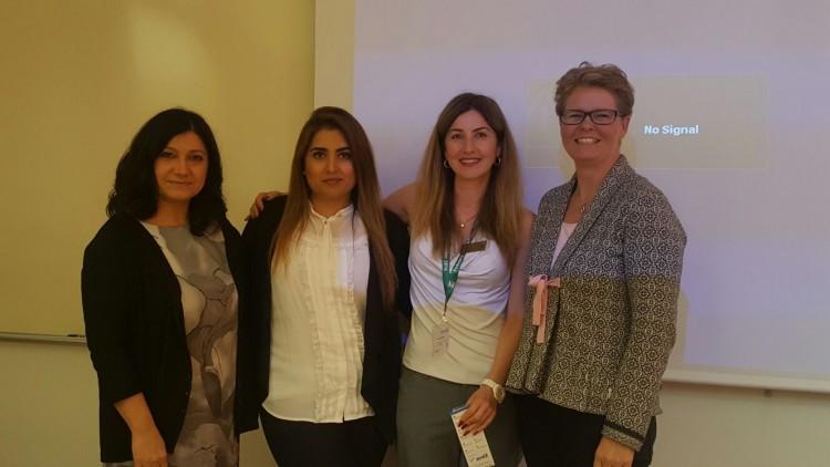 Fyra kvinnor framför projicerad presentation.