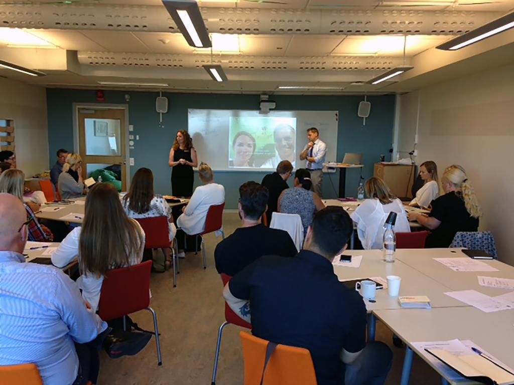 Kvinna och man föreläser framför projicerad presentation.