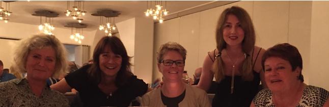 Fem glada kvinnor ler mot kamera.