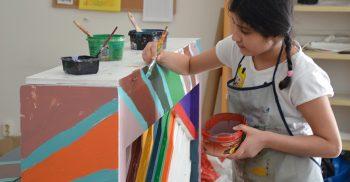 Elev målar piano med färg.