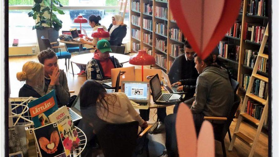 Elever sitter och pluggar i bibliotek.