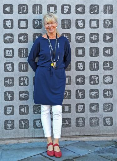 Kvinna står framför vägg med musik- och teatersymboler.