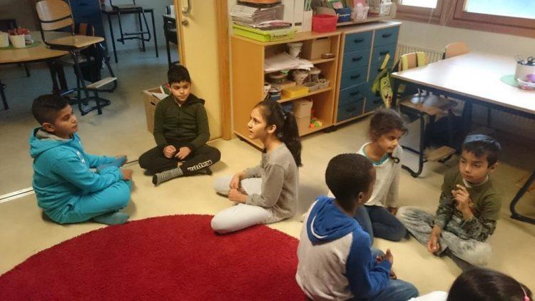 Barn sitter i grupper på golvet.