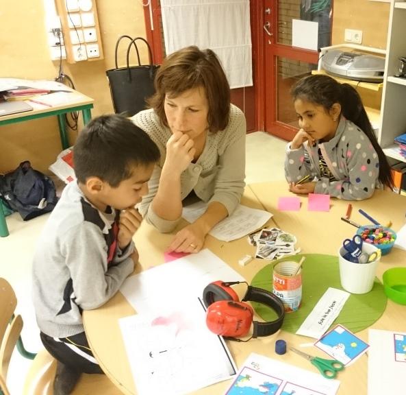 Pedagog sitter med två barn vid bord.
