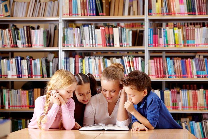 Tre barn och en vuxen läser tillsammans.