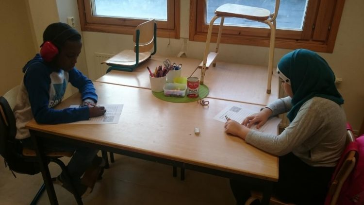 Två elever pluggar vid bord.