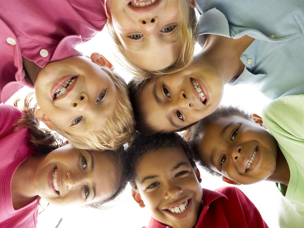 Barn lutar sina huvuden mot varandra och ler.